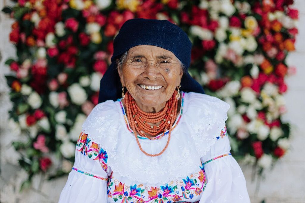 Angelita is sitting at her home with a wall of roses behind her. She is wearing traditional clothing.