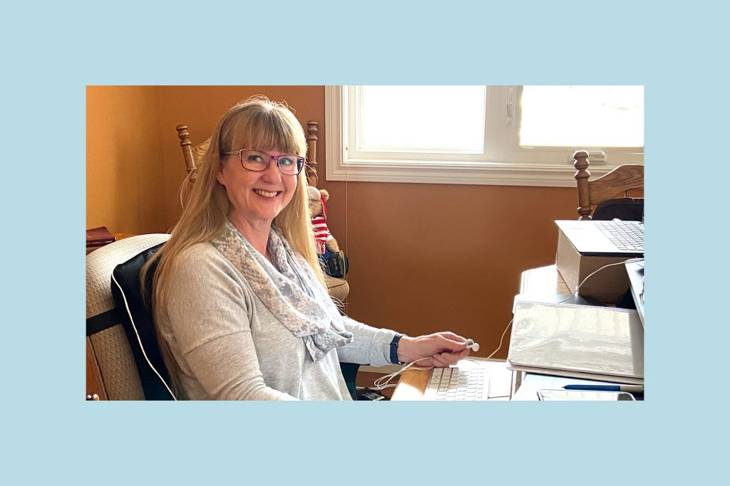 Lynda is wearing glasses and a grey sweater, sitting at her desk in her home office.