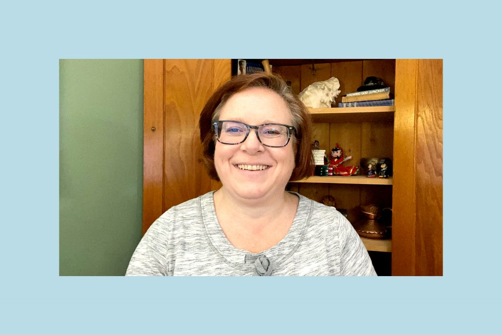 Ruth is smiling and wearing glasses and a grey sweater.
