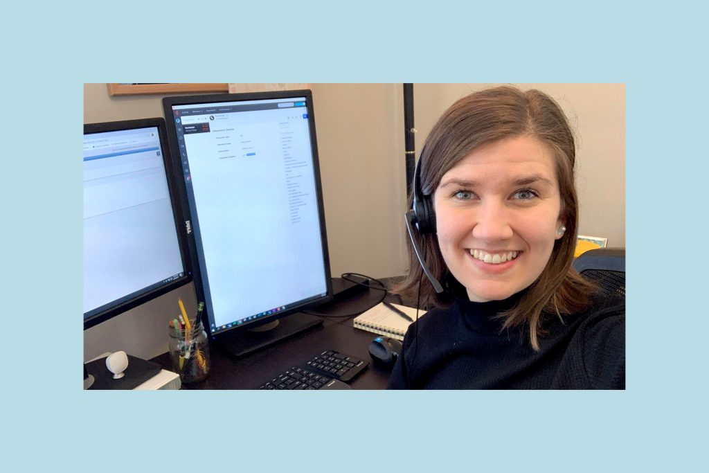 Sueann is wearing a black turtleneck and headset, at her desk in her home office.