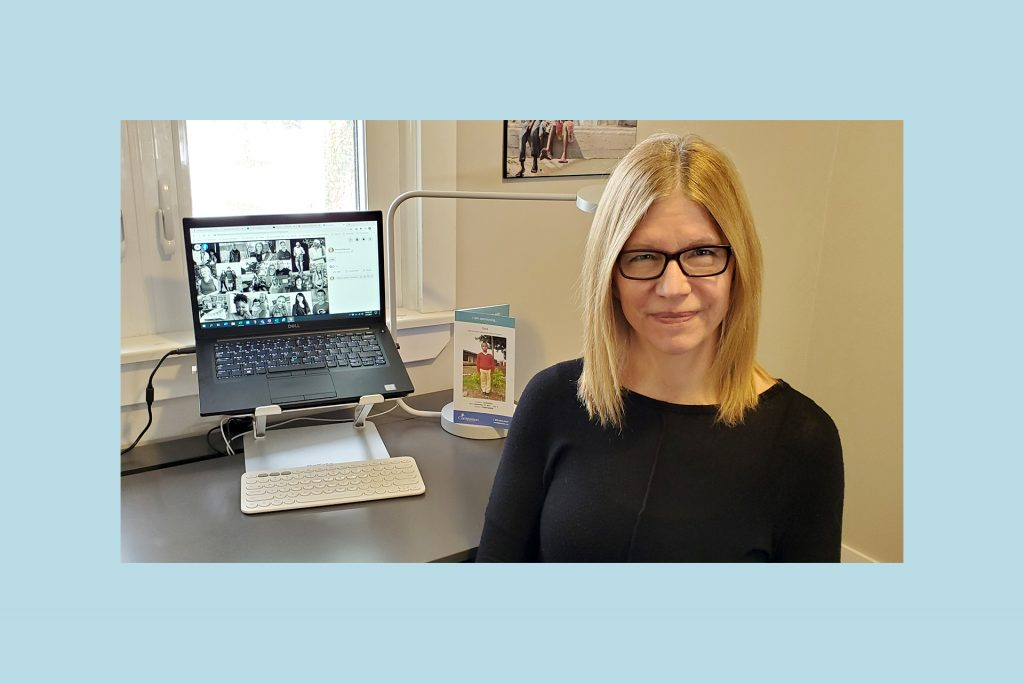 Teresa is wearing glasses and a black shirt, sitting at her desk with her laptop and a photo of her sponsored child behind her.