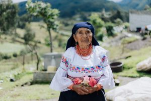 A 91-year-old Ecuadorian woman sits wearing traditional clothing and holding flowers in her hand. Behind her is a field of green grass and trees.