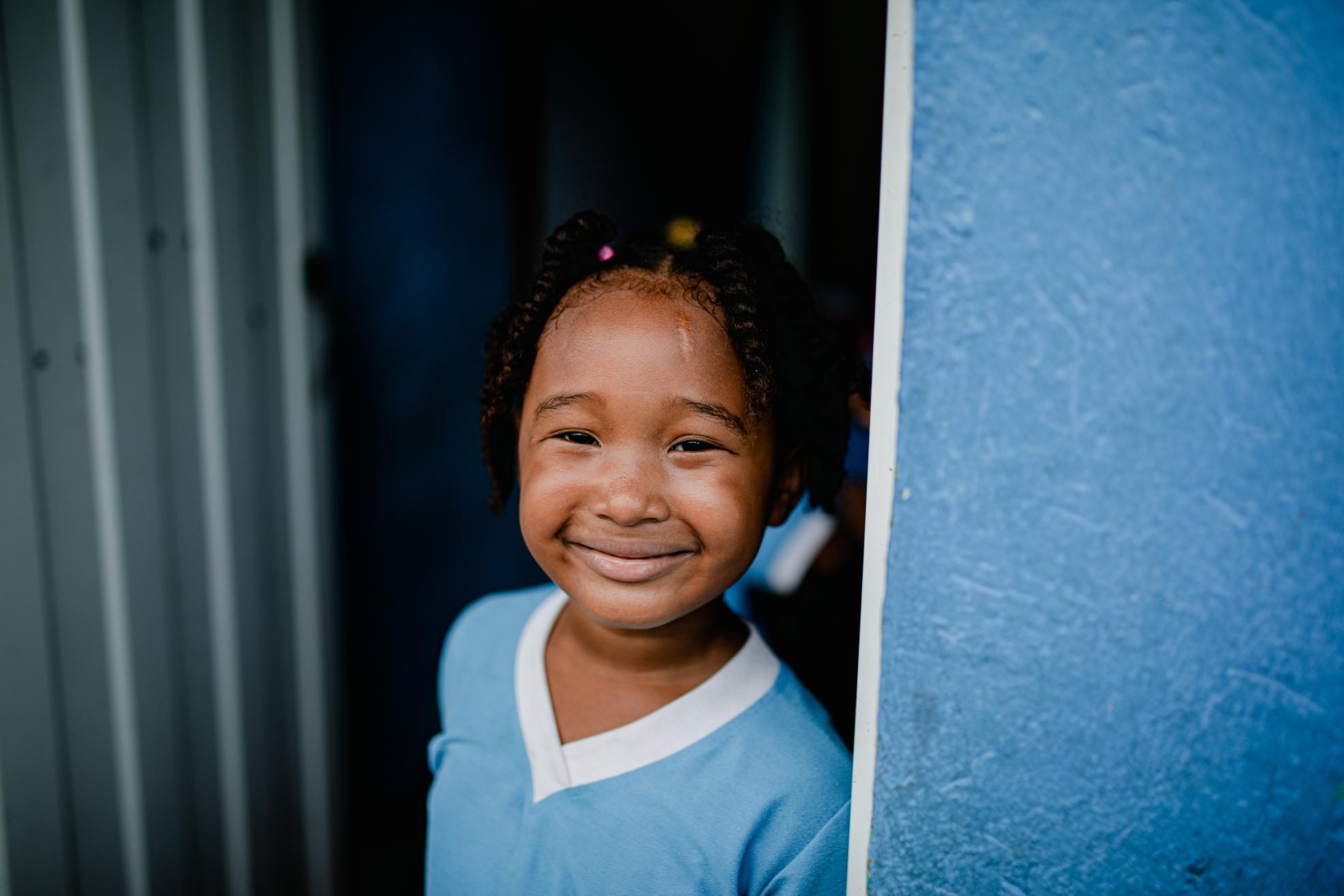Little girl wearing a light blue shirt smiles big in the doorway