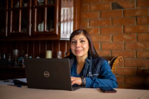 Project Facilitator Virigina sits at her desk behind a Dell laptop. She is wearing a blue jacket with the Compassion logo on it.