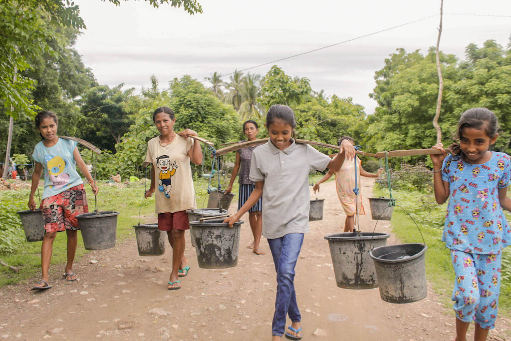 A group of women and girls are carrying water in buckets hanging from yokes on their shoulders. They are walking down a dirt road.