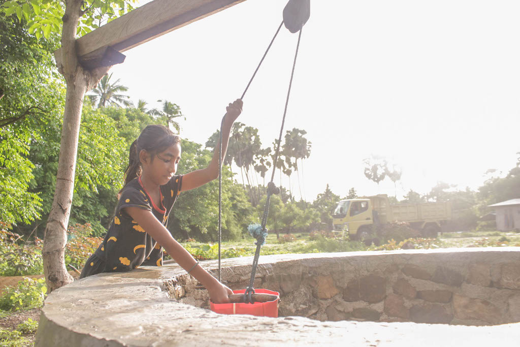 Wearing a black outfit, Yunita collects water from a large well using a red bucket.