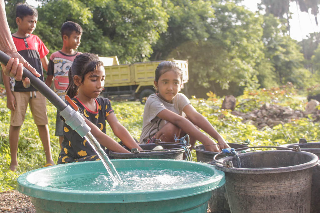 Yunita and other children collect water from the new well in their community.