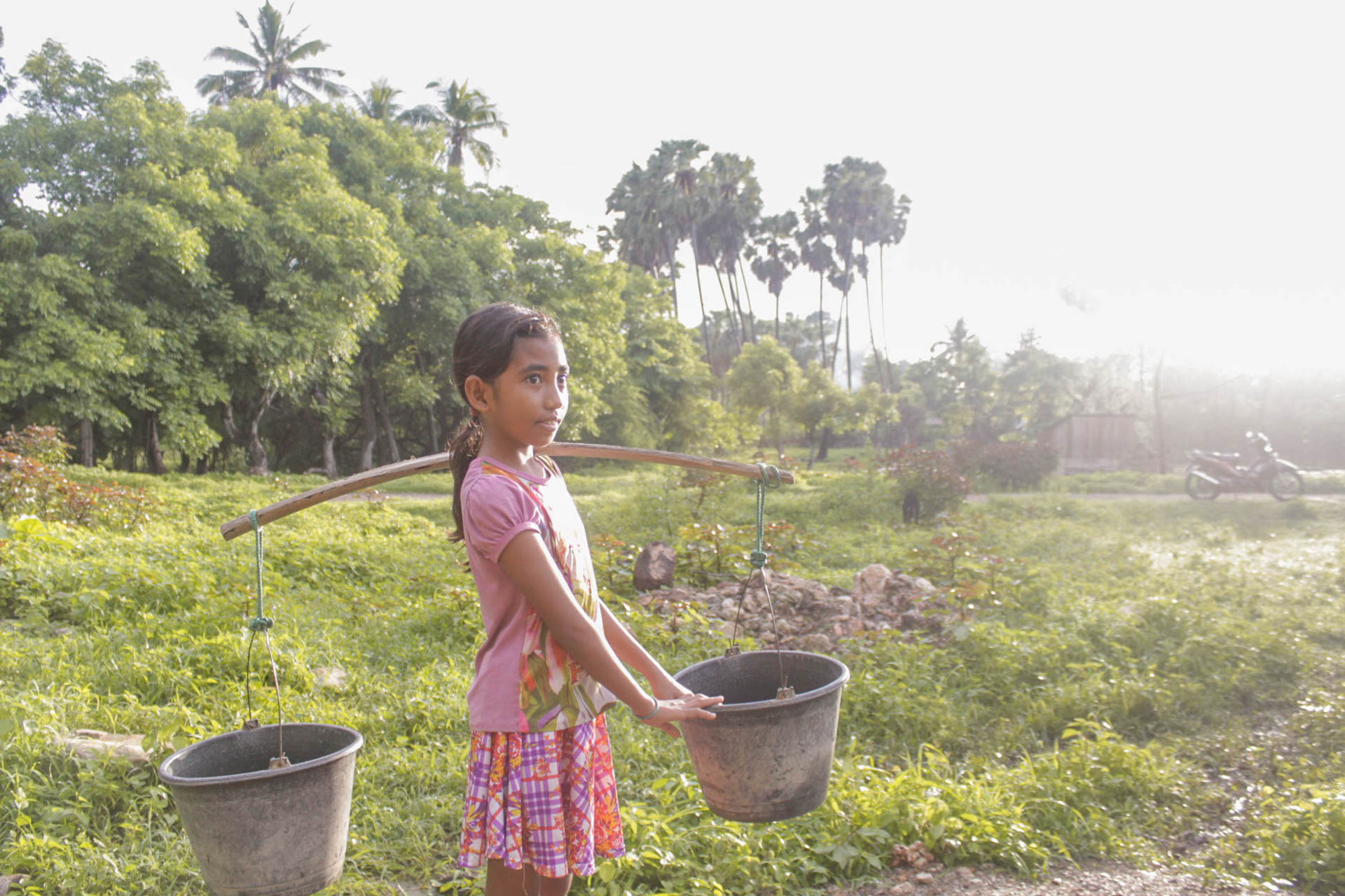 Yunita stands in a green field wearing a pink outfit and carrying a yoke with two water buckets balancing on her shoulder.