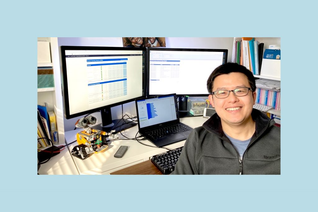 Kevin sits at his desk in his home office with his laptop and two monitors behind him.