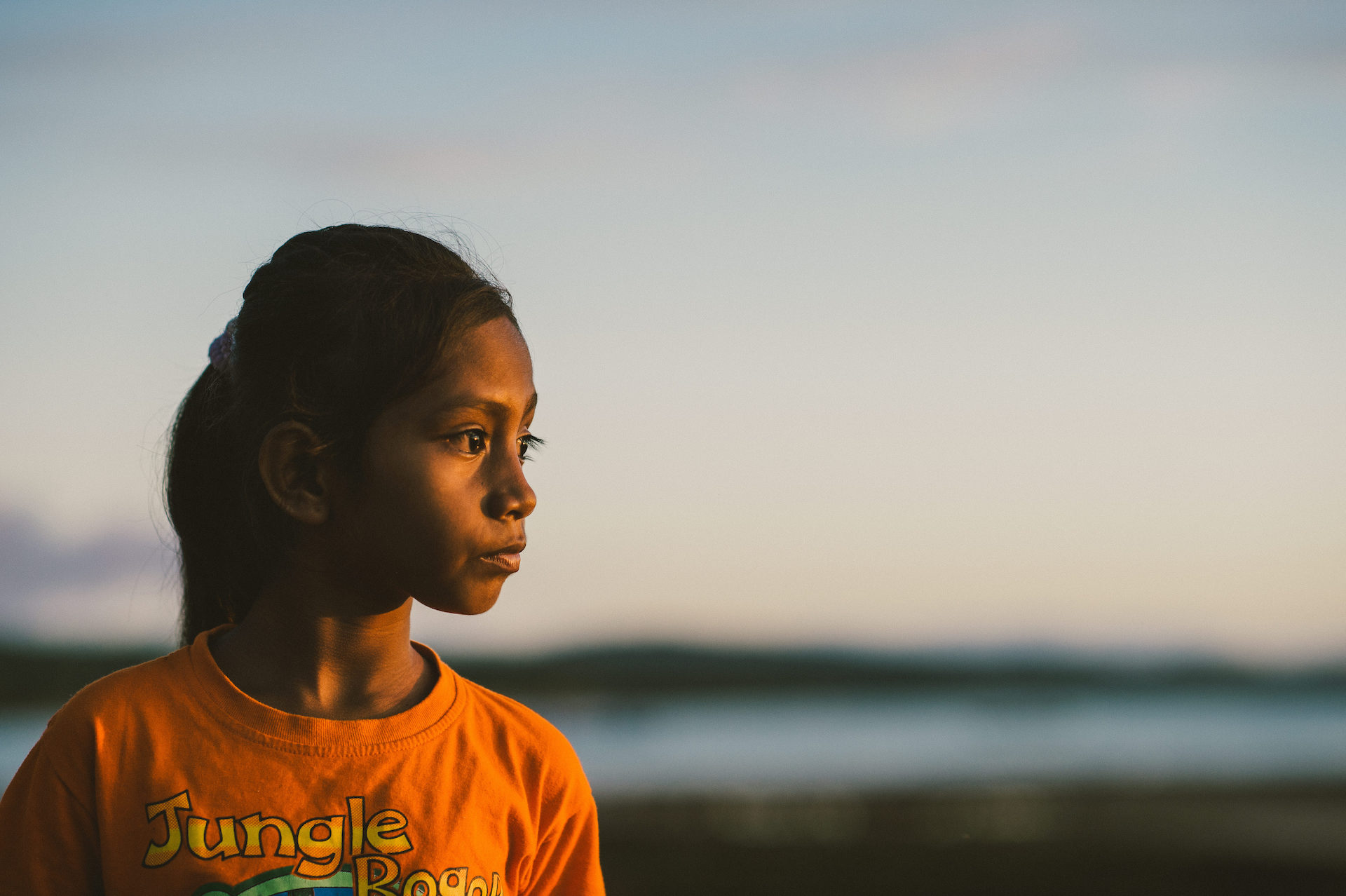 An Indonesian girl wearing an orange t-shirt and a pony tail looks at the sunset.