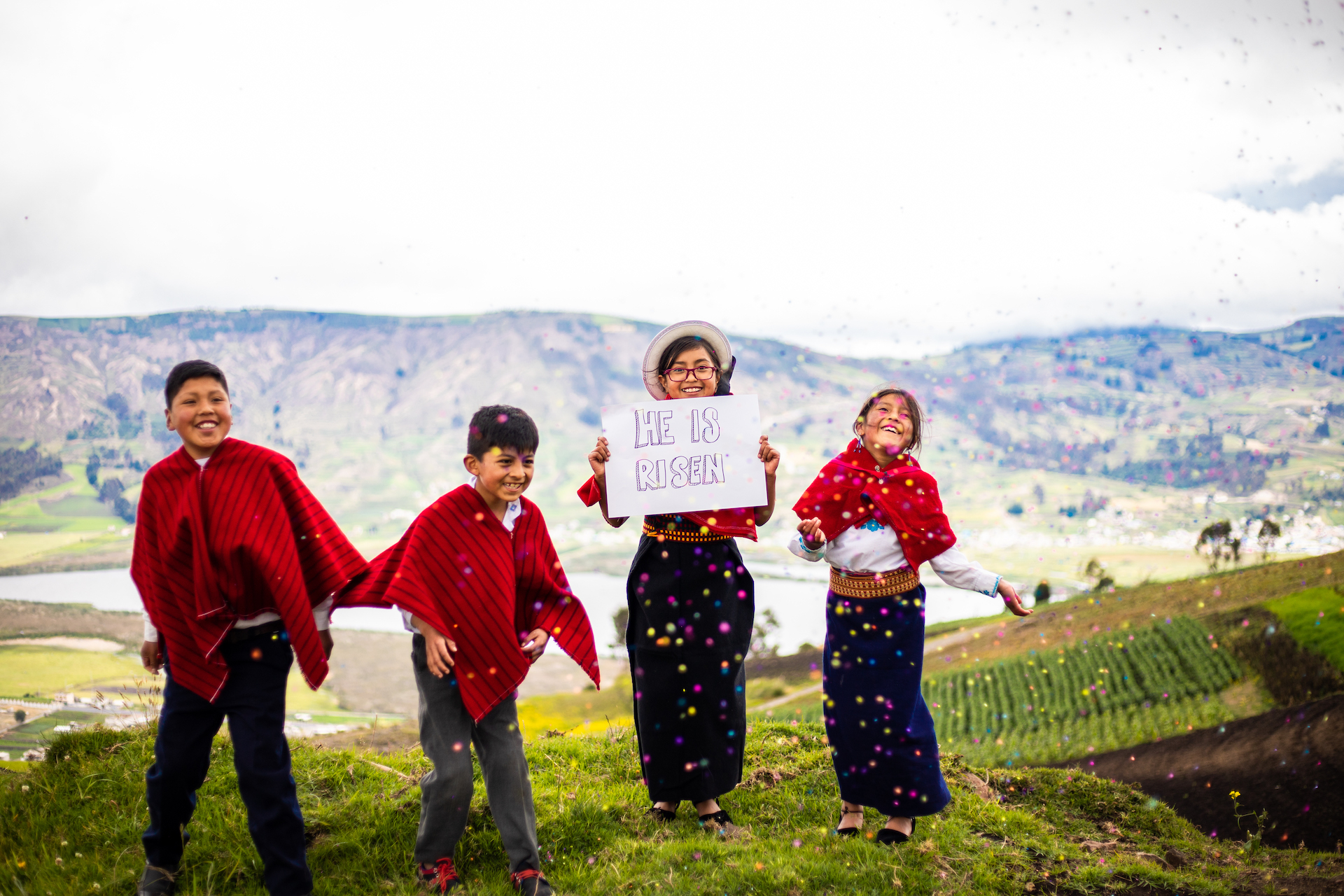 """Cristian, Mateo , Salome, and Sara are playing and throwing confetti while Salome holds a sign that says, """"He is risen."""" They are outside and there is a lake behind them."""