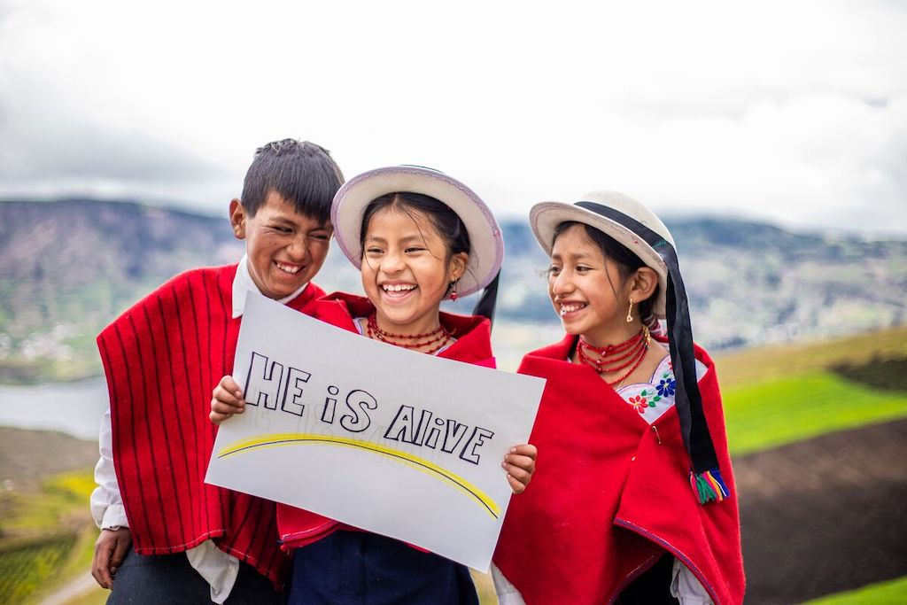 """Cristian, Abigail, and Wilma are wearing traditional clothing and one of the girls is holding a sign that says, """"He is alive."""""""