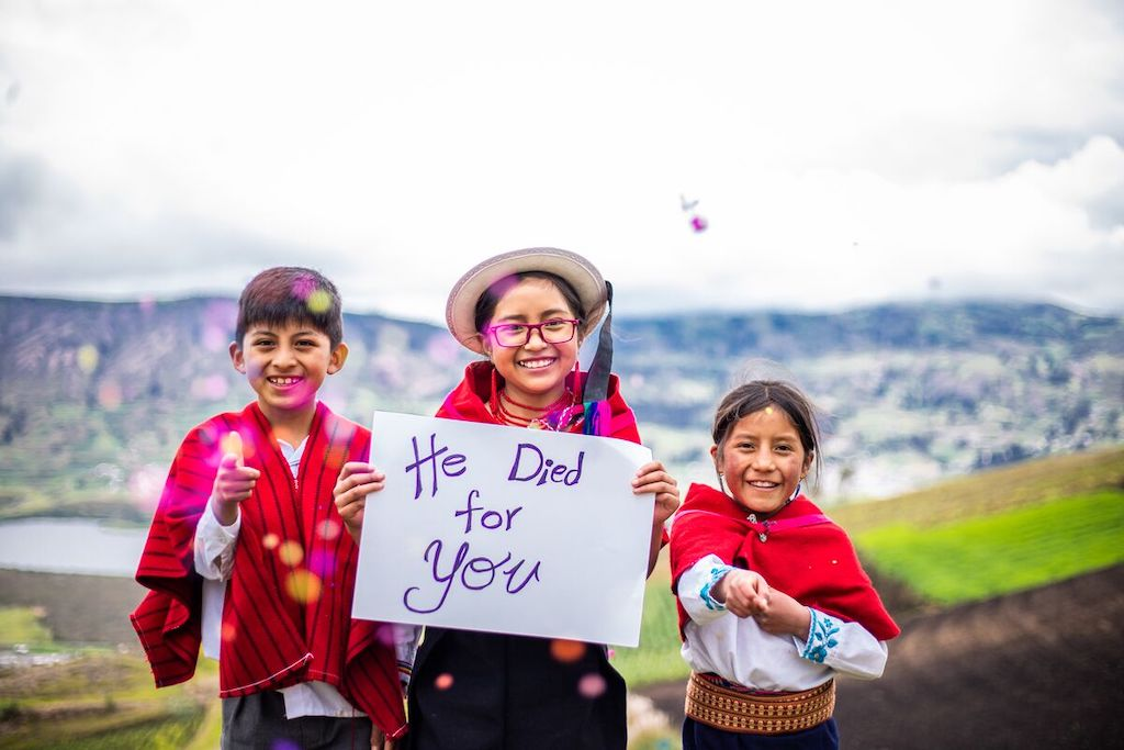"""Mateo, Salome, and Sara, are pointing to the camera. They are wearing traditional clothes and one is holding a sign that says, """"He died for you."""""""