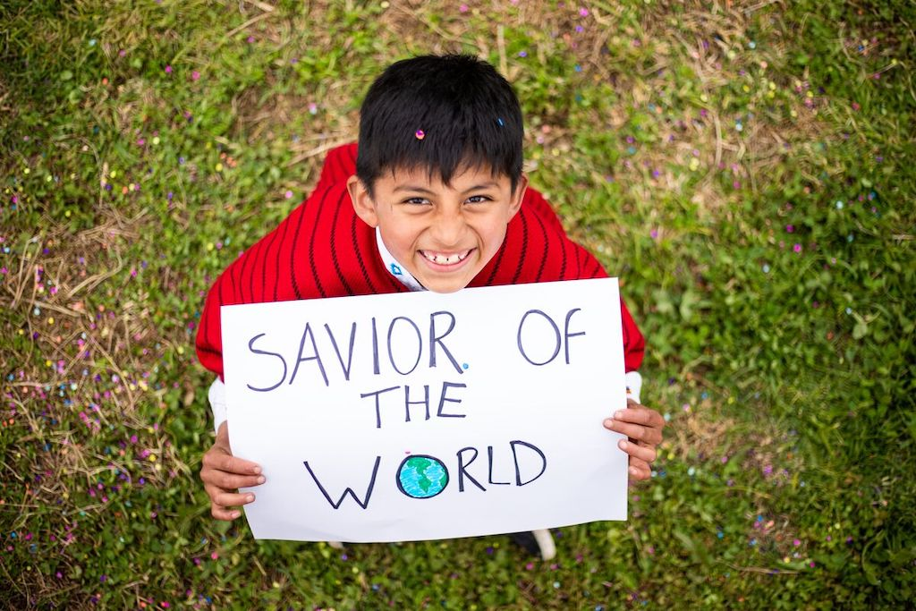 """Mateo is wearing traditional clothing and is holding a sign that says, """"Savior of the World."""""""