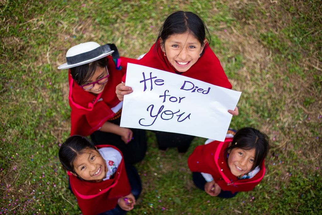 """Vilma, Salome, Sara, and Abigail are all wearing traditional clothing. They are looking up at the camera and Vilma is holding a sign that says, """"He died for you."""""""