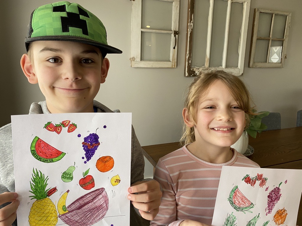 Two kids hold up their finished colouring sheets.