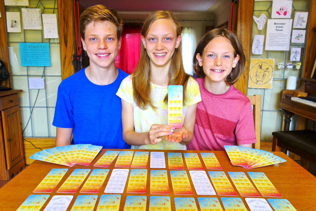 Three siblings sit together at a table with their bookmark product infront of them on the table.