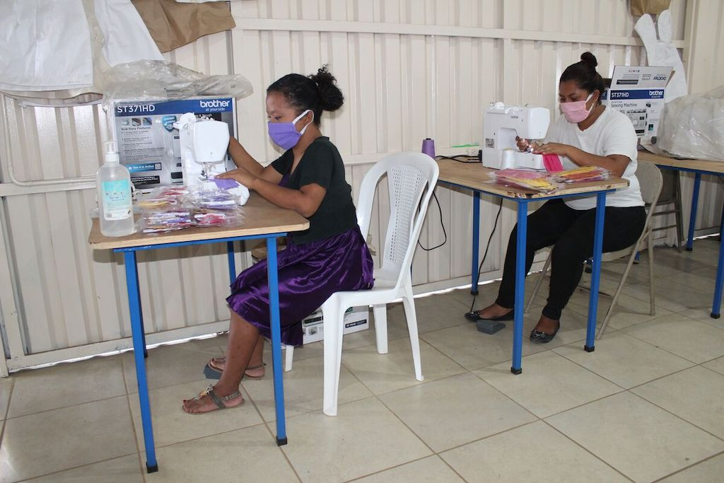 Eveling Sánchez (left) is wearing a black shirt and a purple skirt. Leticia Mayorga (right) is wearing a white shirt and black pants. They are sitting at sewing machines and are making masks.
