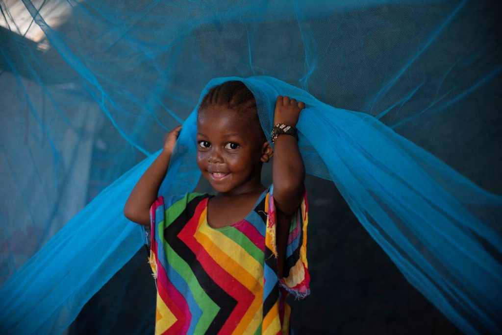 Suzanna, Grace's daughter, is wearing a colorful dress and is sitting under a blue mosquito net. She is smiling at the camera.