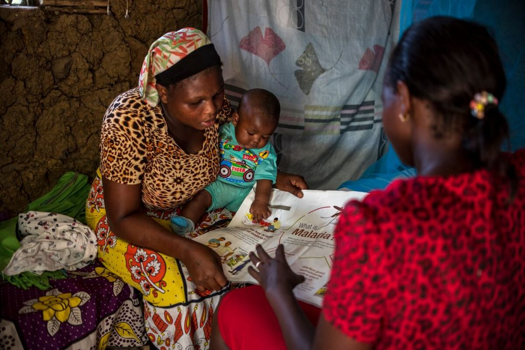Grace is sitting in her home, wearing a brown and black animal print dress with a yellow patterned skirt. She is holding Emmanuel in her lap and talking to another woman in a red dress about malaria.