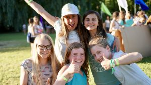 A group of five girls pose together at camp.