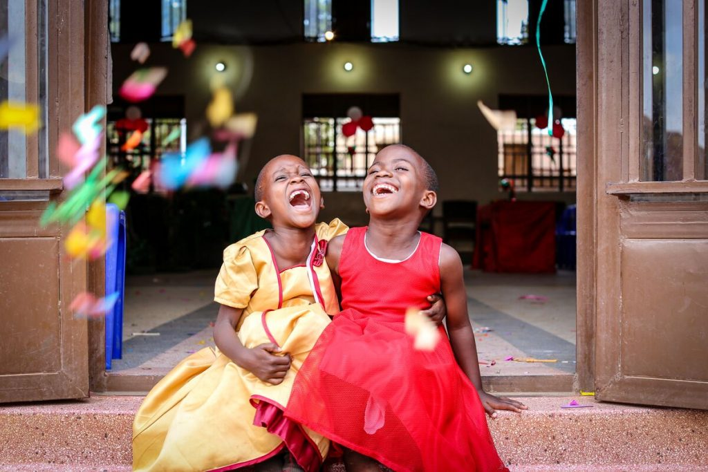 Two girls are seen here, seated in an open doorway to the church/project. The girls are both wearing dresses, one is wearing yellow and the other is wearing red. They are smiling and have their arms around one another, and have tossed confetti into the air.