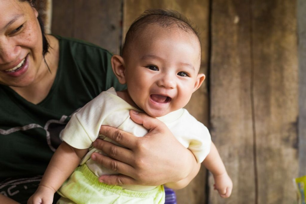 A baby is smiling at the camera in front of a wooden wall.