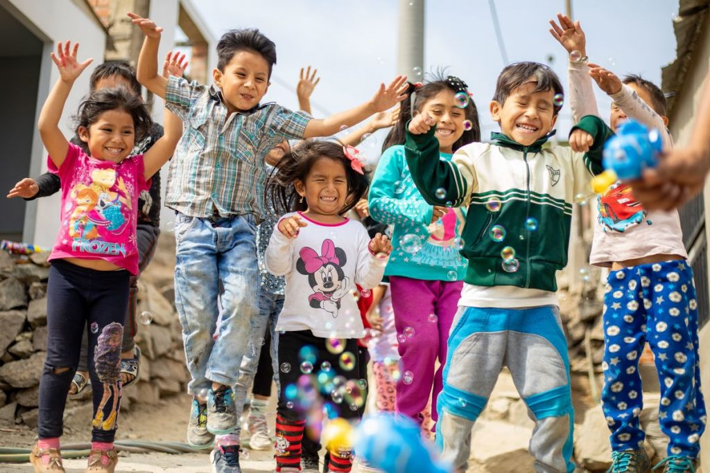 A large group of children playing with bubbles outside the project. They are happy and smiling, and jumping with their arms up.