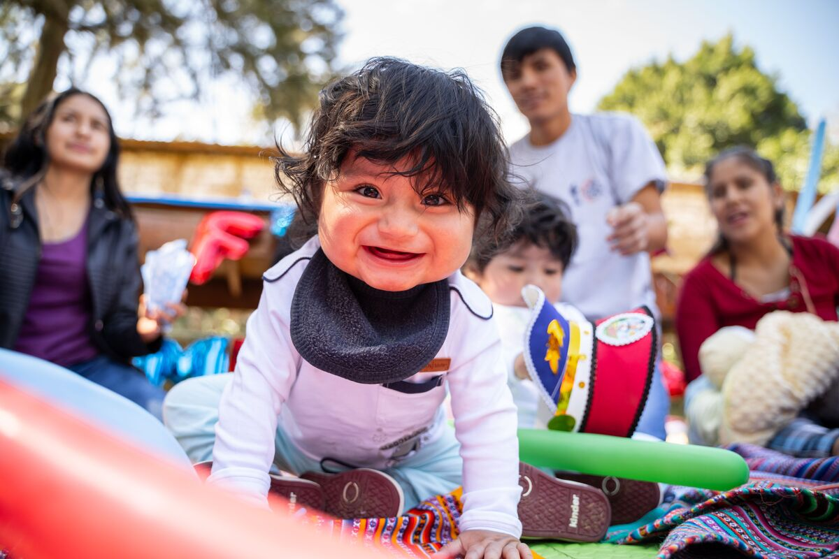 A baby is wearing a white shirt and a black bib. He is smiling at the camera. He is playing outside and is surrounded by survival program mothers.