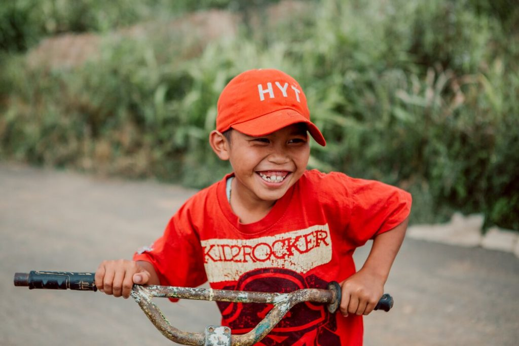 A boy in red smiles while holding onto his bike handles.