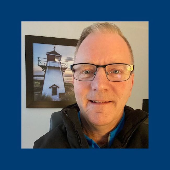 Pastor Jay wearing glasses and a dark jacket, in front of a photo of a lighthouse.