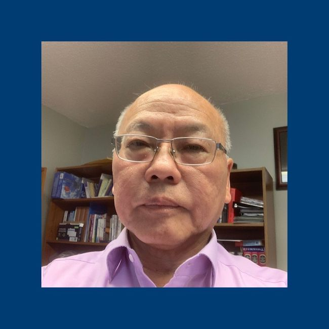 Pastor Ming wearing glasses and a purple collared shirt