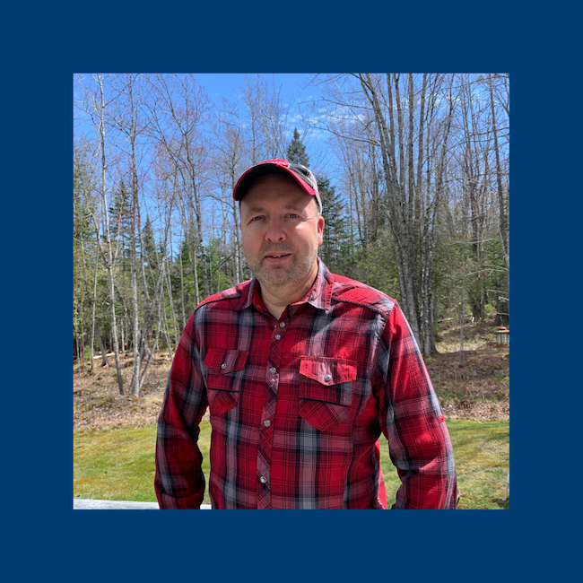 Pastor Brent wearing a baseball cap and a red plaid shirt.