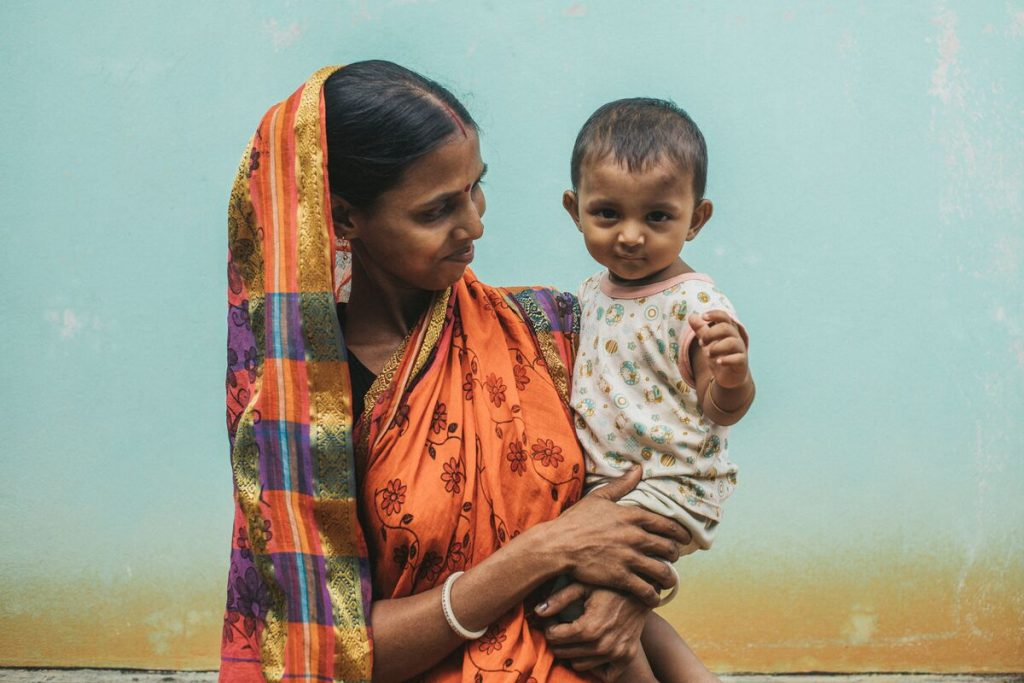 A mother is standing in front of a light blue wall wearing an orange saari with her child in her arms. She is looking at her child and smiling.
