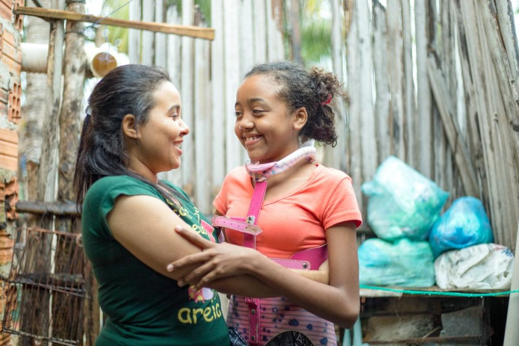 A girl in an orange shirt hugs her mother in a green shirt. They look at each other and smile.