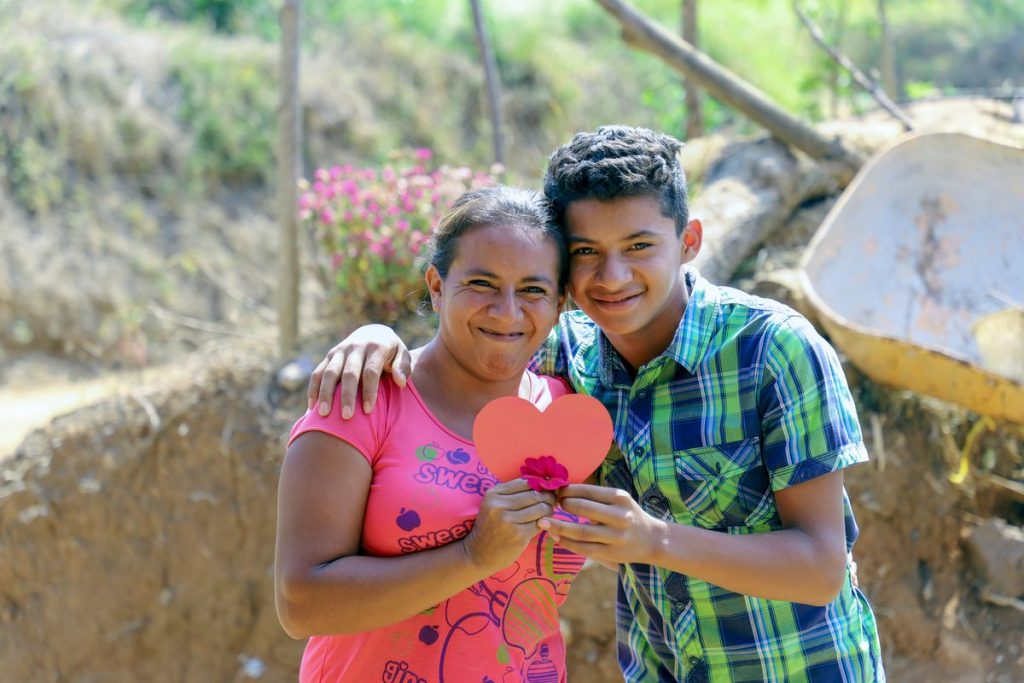 A boy in a blue and green shirt and his mother in a pink shirt hold a heart shape and a flower as they smile.