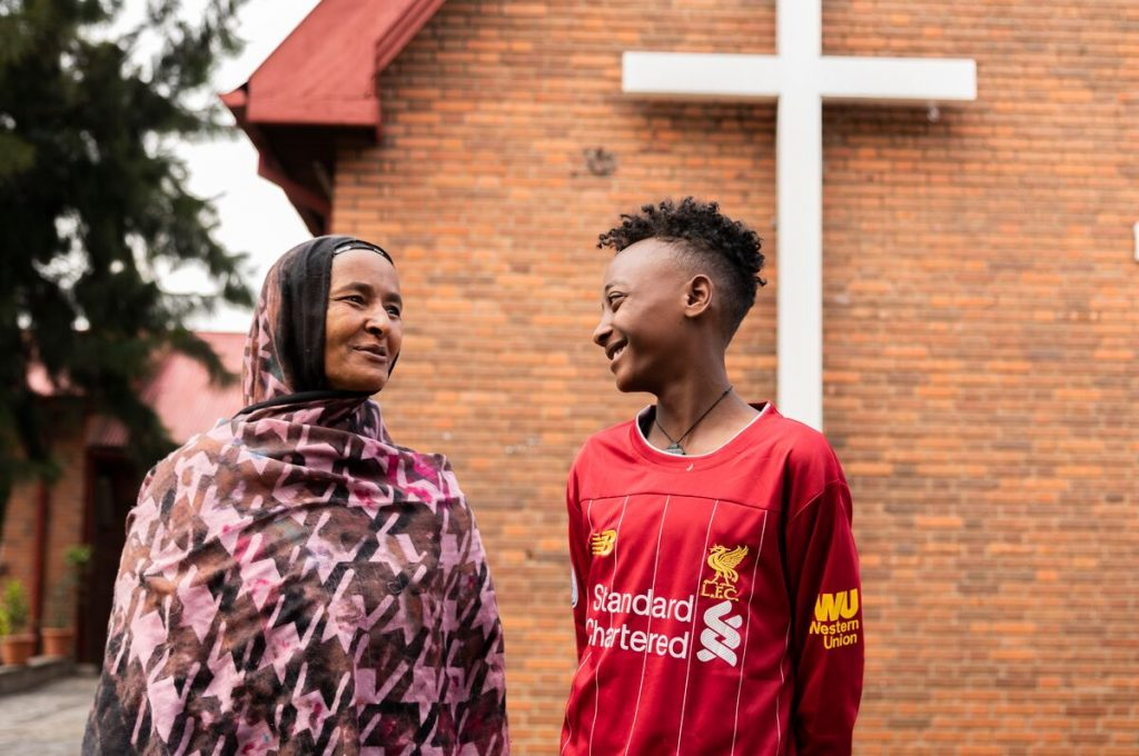 A teen boy is wearing a red shirt. He is standing outside with his mother, who is wearing a pink and brown patterned shawl. They are standing in front of a brick building and talking to each other.