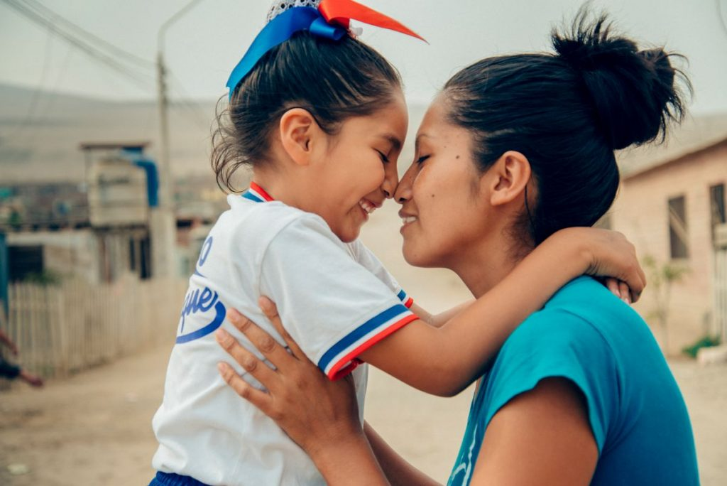 A young girl held by her mom. She is wearing red, white and blue ribbons bows in her hair. She leans in to touch her nose to her mom's nose.