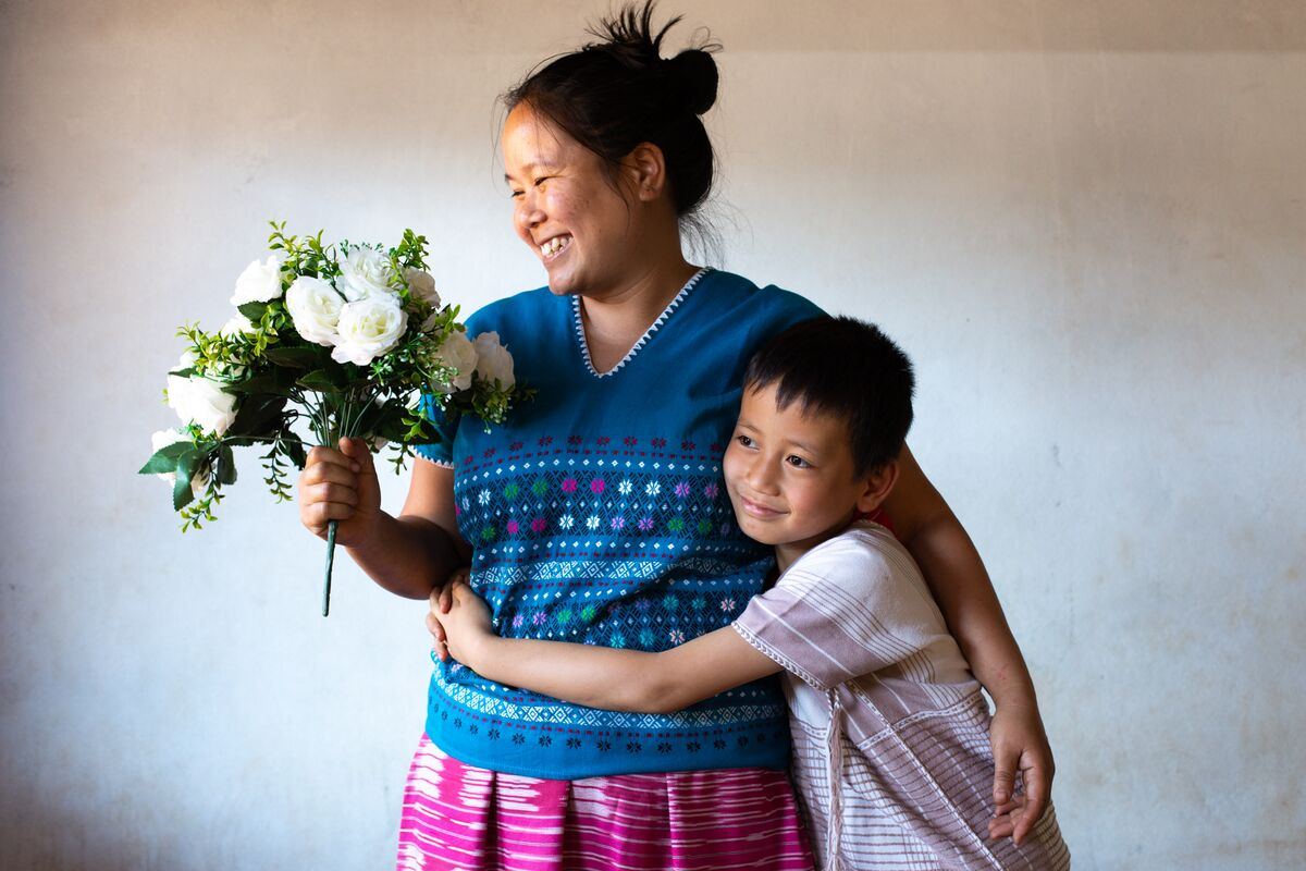 A small boy is wearing a white shirt. He is with his mother who is wearing a blue shirt and a pink skirt. He has his arms around his mother and she is holding a bouquet of white flowers.