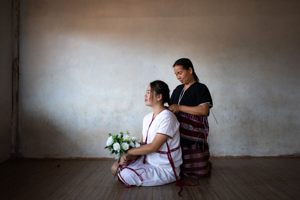 A teen girl is wearing a white shirt and she is with her mother who is wearing a black shirt. She is holding a bouquet of white flowers and her mother is braiding her hair. They are in a white room.