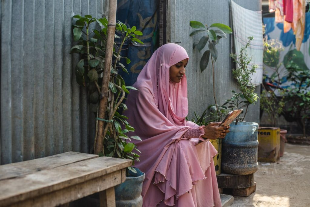 Akhi is wearing a pink dress and head covering. She is sitting in the doorway of her home and is reading a letter from her sponsor. Her home is made of corrugated metal.