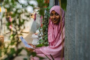 Akhi is wearing a pink dress and head covering. She is sitting in the doorway of her home and is holding a letter from her sponsor.