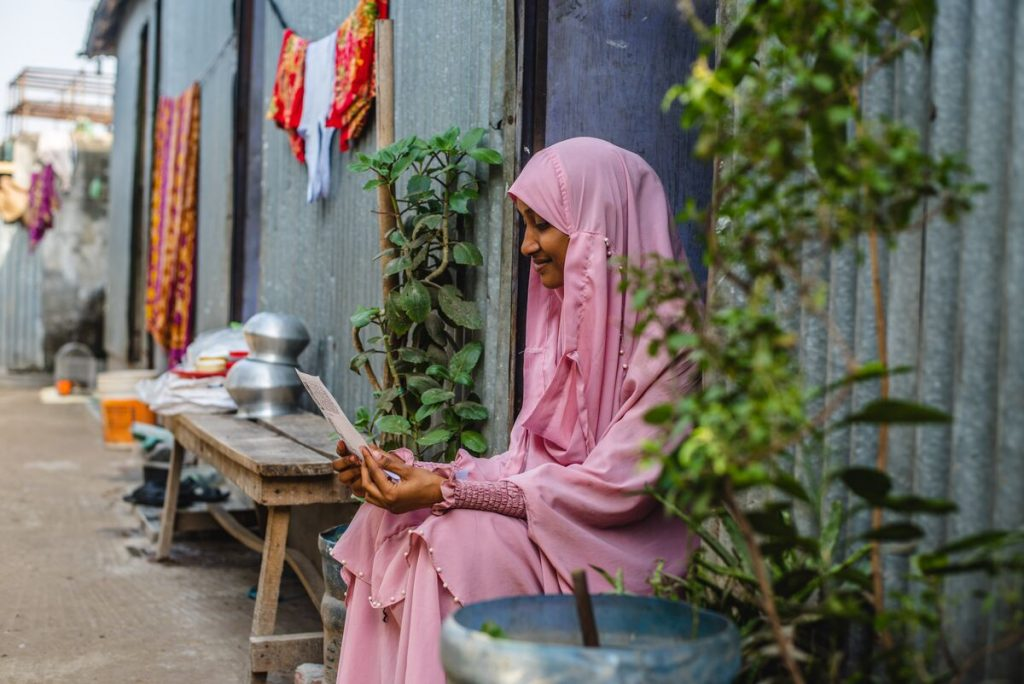 Akhi is wearing a pink dress and head covering. She is sitting in the doorway of her home and is holding a letter from her sponsor. Her home is made of corrugated metal.