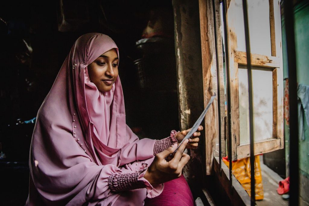 Akhi is wearing a pink dress and head covering. She is sitting in front of a window in her home and is looking at a letter from her sponsor.