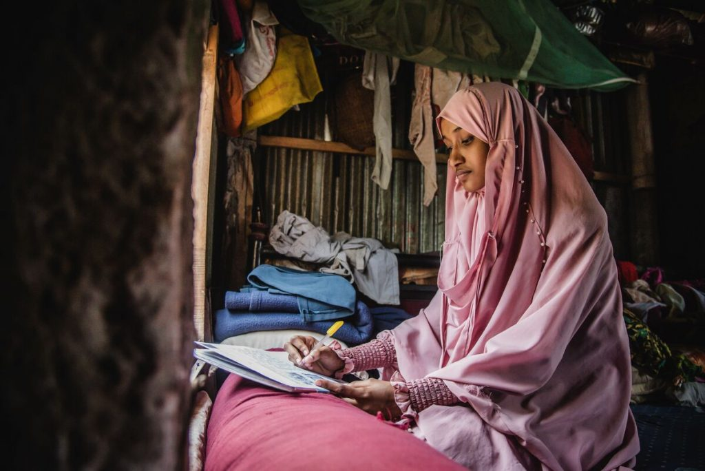 Akhi is wearing a pink dress and head covering. She is sitting in front of a window in her home and is writing a letter to her sponsor.