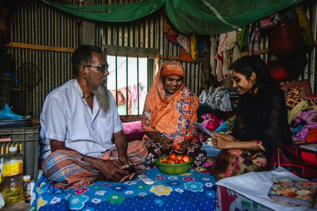 Akhi, wearing a black shirt, is sitting on the bed with her mother and father, and is reading them a letter from her sponsor. Her mother is wearing an orange patterned dress and head covering. Her dad is wearing a light blue shirt. They are sitting on a blue floral print sheet.
