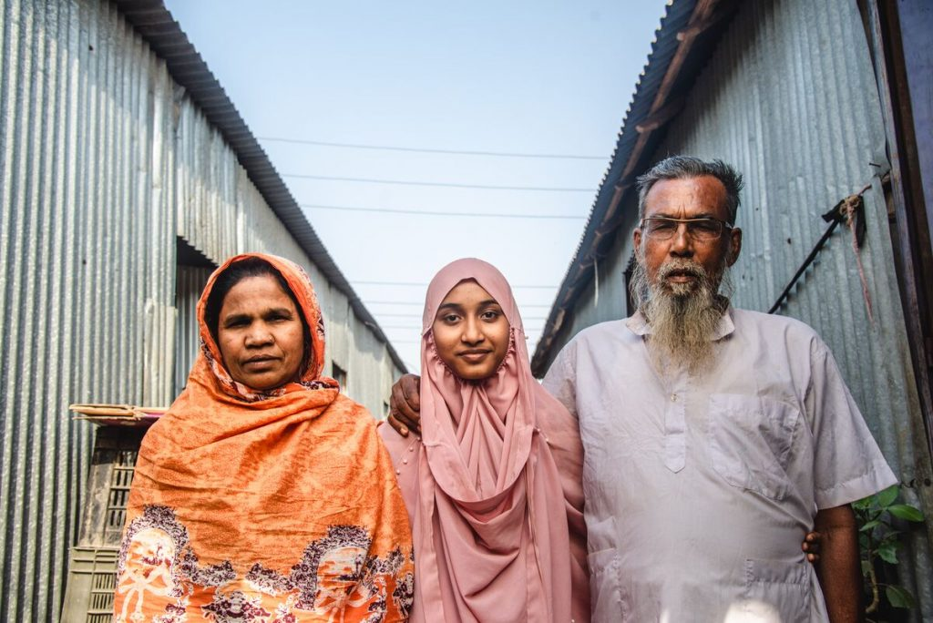 Akhi is wearing a pink dress and head covering. She is standing outside her home with her mother, wearing an orange dress and head covering, and her father, wearing a light gray shirt. They have their arms around each other.