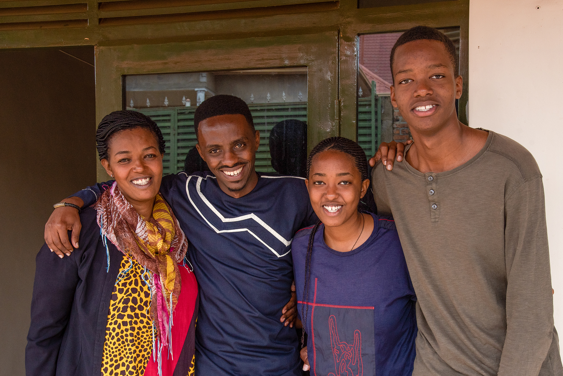 Left to right, Christian's aunt Pascasie, Christian, and his cousins Cynthia and Mugisha stand with their arms around each other.