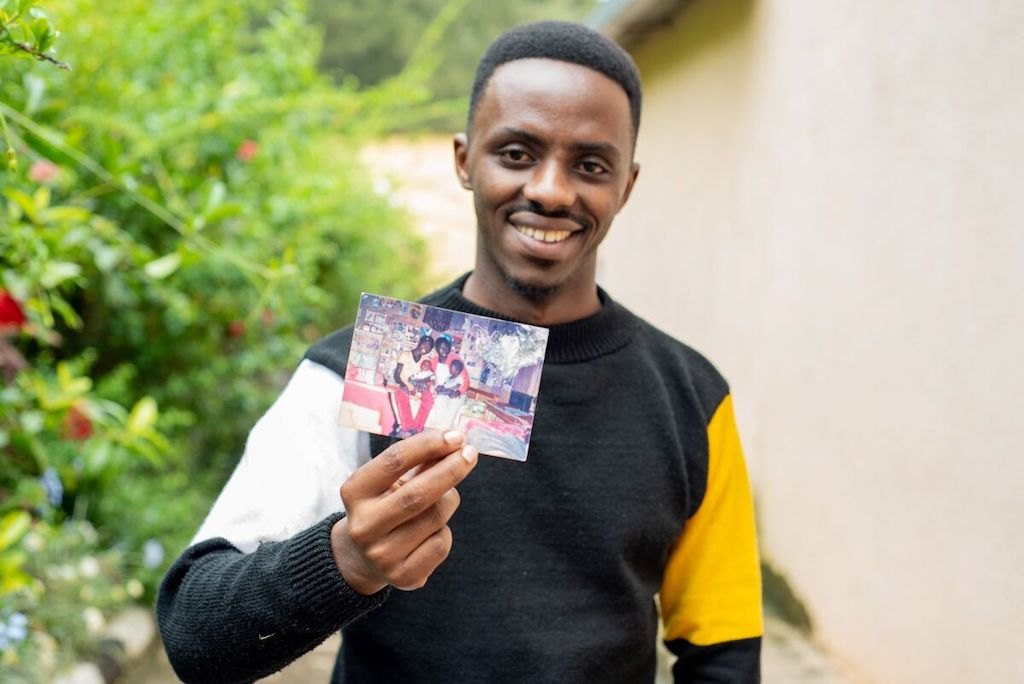 Christian smiles and holds up a printed photograph of his father holding him as a baby.