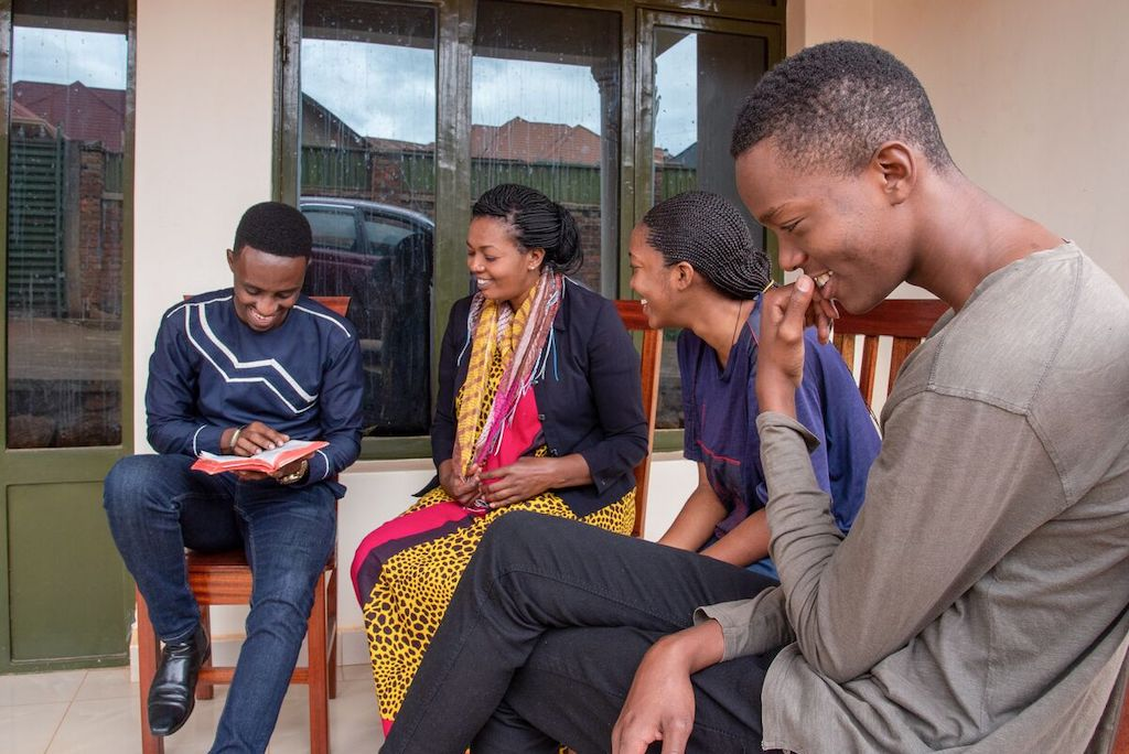 Christian, his aunt Pascasie and his cousins Cynthia and Mugisha sit on the porch together.